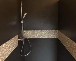Réalisation d'un espace douche avec panneaux Touch et une frise de galets